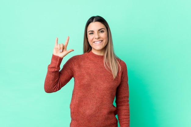 Young caucasian woman isolated showing a horns gesture as a revolution concept.