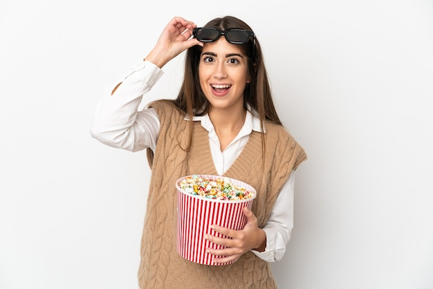 Young caucasian woman isolated surprised with 3d glasses and holding a big bucket of popcorns