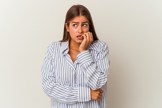 Young caucasian woman isolated on white background blink through fingers frightened and nervous.