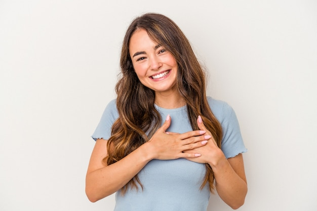 Young caucasian woman isolated on white background has friendly expression, pressing palm to chest. love concept.
