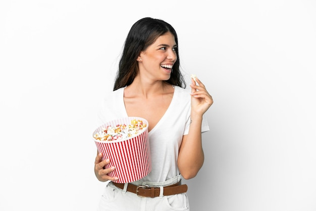 Young caucasian woman isolated on white background holding a big bucket of popcorns