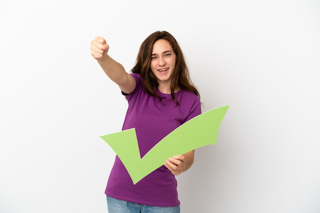 Young caucasian woman isolated on white background holding a check icon and celebrating a victory