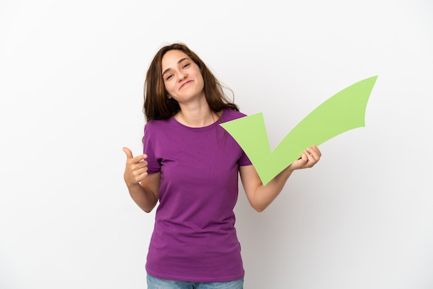 Young caucasian woman isolated on white background holding a check icon and pointing it