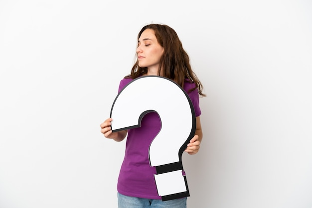 Young caucasian woman isolated on white background holding a question mark icon and looking side