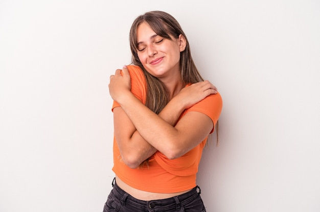 Young caucasian woman isolated on white background hugs, smiling carefree and happy.