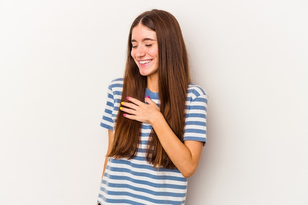 Young caucasian woman isolated on white background laughing keeping hands on heart, concept of happiness.