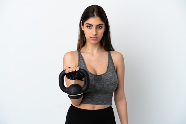 Young caucasian woman isolated on white background making weightlifting with kettlebell and looking to the front