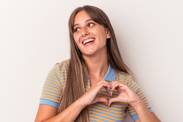 Young caucasian woman isolated on white background smiling and showing a heart shape with hands.