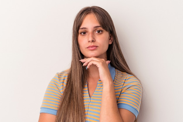 Young caucasian woman isolated on white background suspicious, uncertain, examining you.
