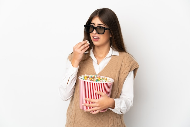 Young caucasian woman isolated on white background with 3d glasses and holding a big bucket of popcorns while looking side