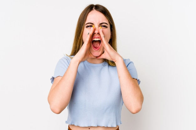 Young caucasian woman isolated on white shouting excited to front.