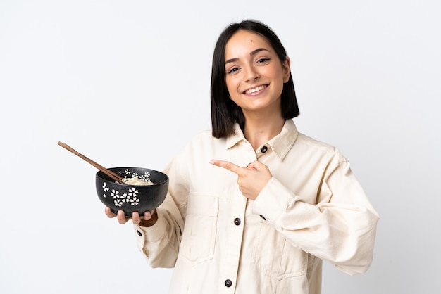 Young caucasian woman isolated on white wall and pointing it while holding a bowl of noodles with chopsticks