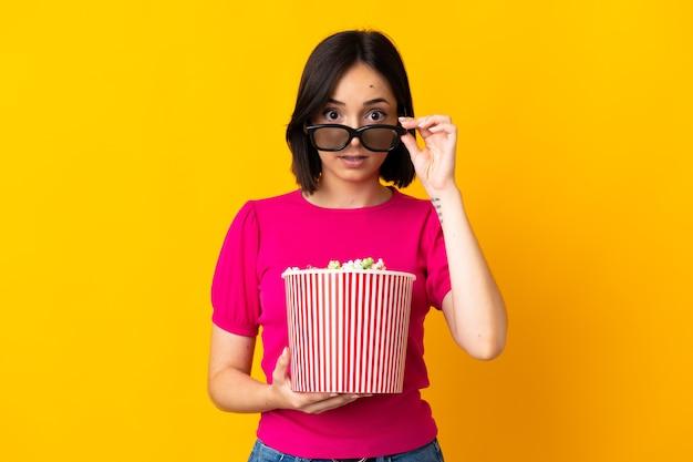 3dメガネで隔離され、ポップコーンの大きなバケツを保持している若い白人女性