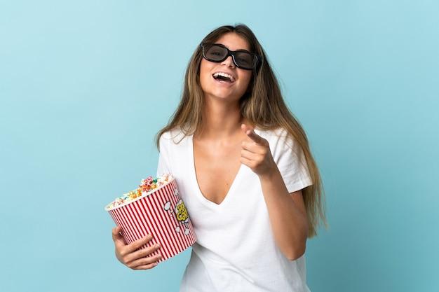 Молодая кавказская женщина изолирована в 3d-очках и держит большое ведро попкорна