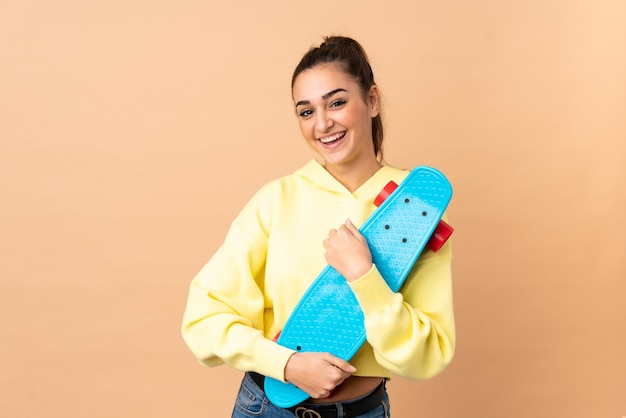 Young caucasian woman isolated with a skate with happy expression