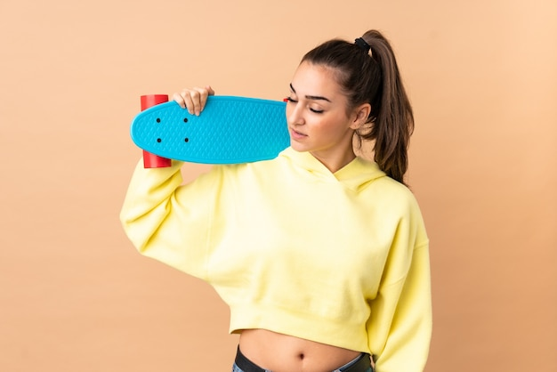 Young caucasian woman isolated with a skate