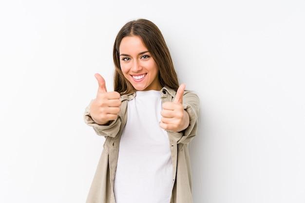 Молодая кавказская женщина изолирована с большими пальцами руки вверх, приветствует что-то