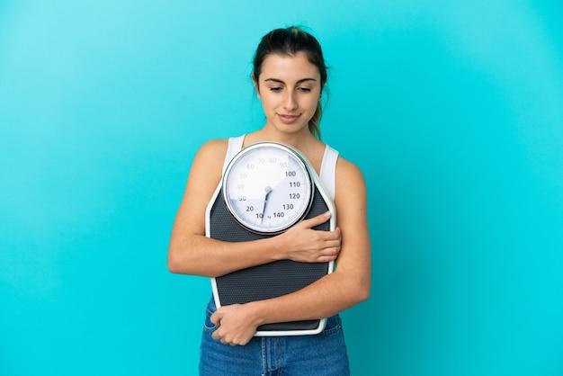体重計で分離された若い白人女性