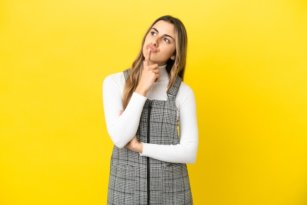 Young caucasian woman isolated on yellow background having doubts while looking up