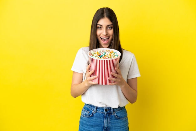 Young caucasian woman isolated on yellow background holding a big bucket of popcorns