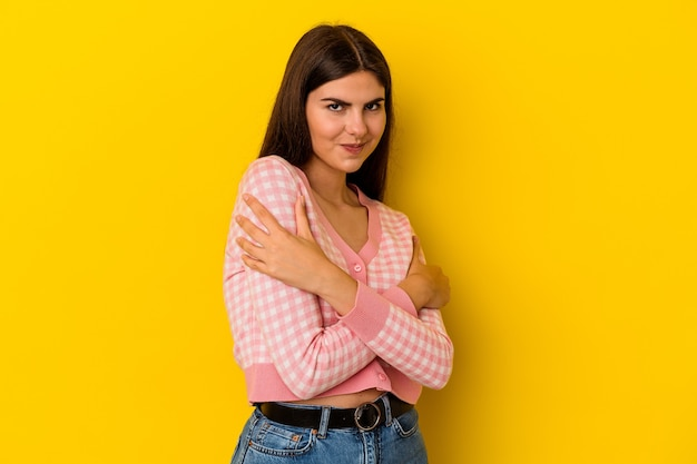 Young caucasian woman isolated on yellow background hugs, smiling carefree and happy.