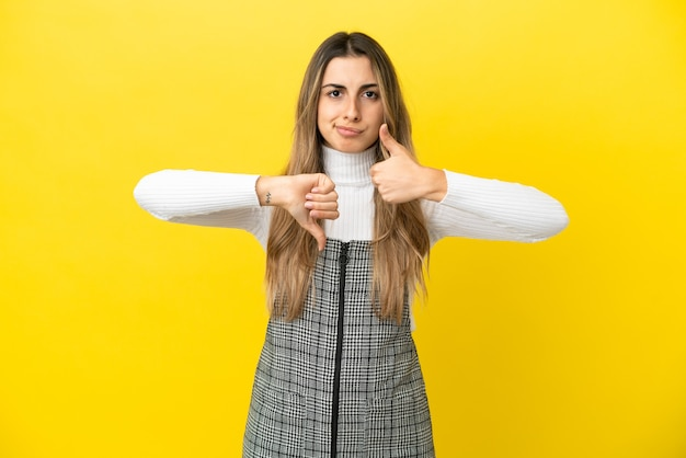 Young caucasian woman isolated on yellow background making good-bad sign. undecided between yes or not