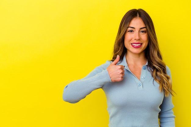 Young caucasian woman isolated on yellow background smiling and raising thumb up