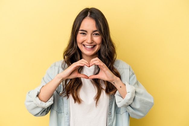 Young caucasian woman isolated on yellow background smiling and showing a heart shape with hands.