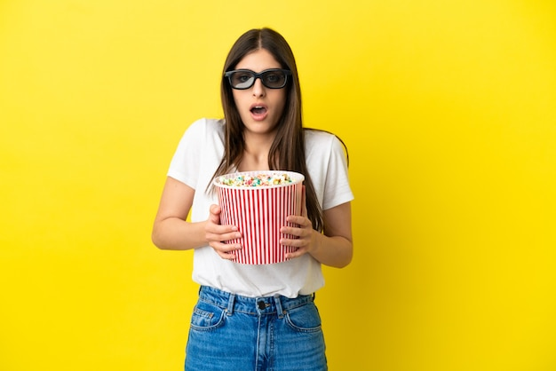 Young caucasian woman isolated on yellow background surprised with 3d glasses and holding a big bucket of popcorns