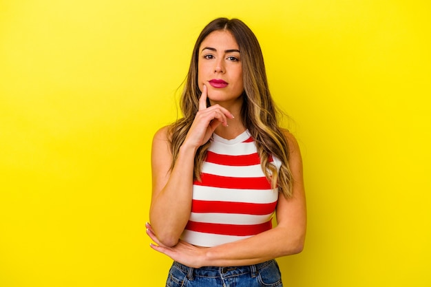 Young caucasian woman isolated on yellow background suspicious, uncertain, examining you.