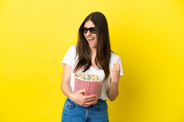 Young caucasian woman isolated on yellow background with 3d glasses and holding a big bucket of popcorns while looking side
