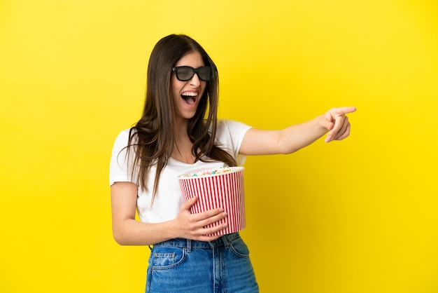Young caucasian woman isolated on yellow background with 3d glasses and holding a big bucket of popcorns while pointing away