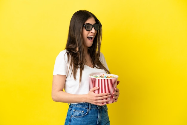 Young caucasian woman isolated on yellow background with 3d glasses and holding a big bucket of popcorns
