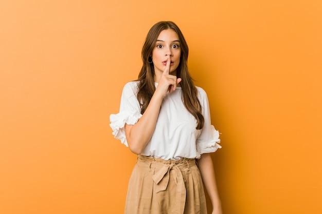 Молодая кавказская женщина хранит секрет или просит молчания.