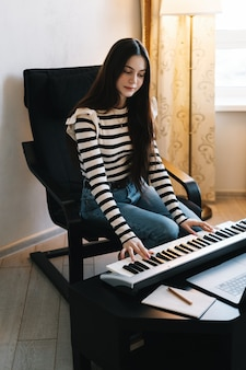 Young caucasian woman learns to play the piano keys using a laptop at home distantly.