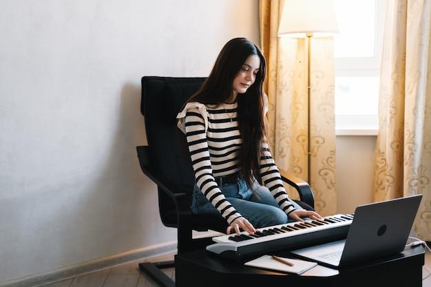 Молодая кавказская женщина учится играть на клавишах пианино с помощью ноутбука дома удаленно.