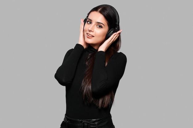 Молодая кавказская женщина слушает музыку в беспроводных наушниках на изолированном фоне