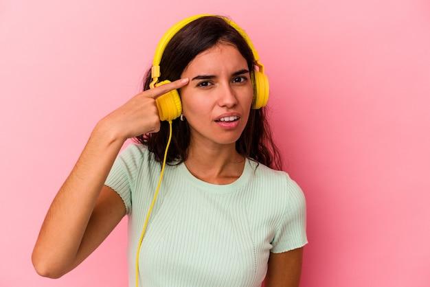 人差し指で失望のジェスチャーを示すピンクの背景に分離された音楽を聞いている若い白人女性。