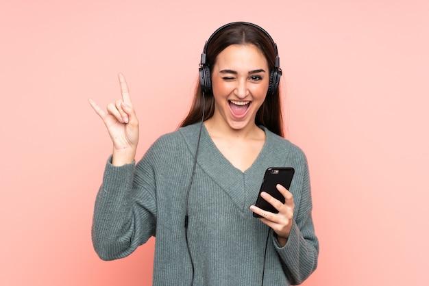 Молодая кавказская женщина слушает музыку с помощью мобильного телефона