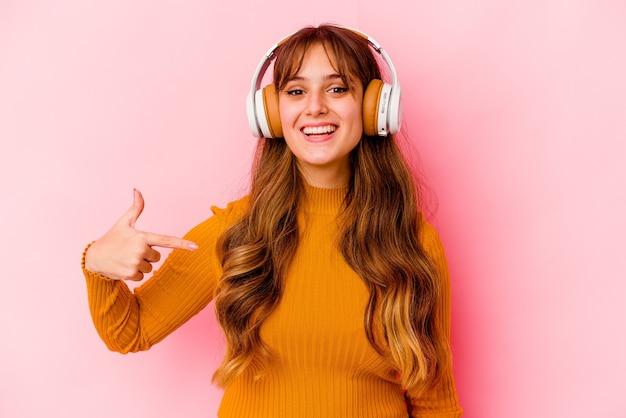 Молодая кавказская женщина, слушающая музыку в наушниках, изолировала человека, указывающего рукой на пространство для копирования рубашки, гордая и уверенная в себе