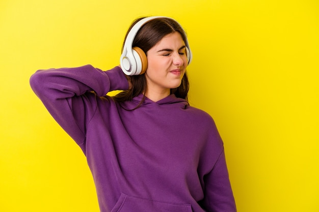 Young caucasian woman listening to music with headphones isolated on pink suffering neck pain due to sedentary lifestyle.