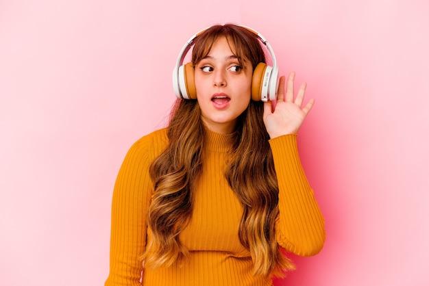 Молодая кавказская женщина слушает музыку с изолированными наушниками, пытаясь слушать сплетню.