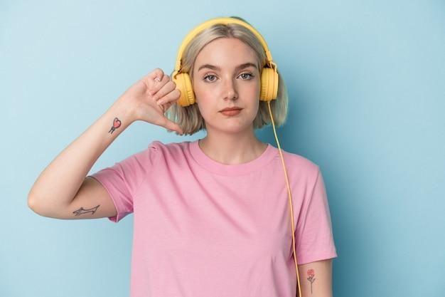 嫌いなジェスチャーを示す青い背景で隔離の音楽を聞いている若い白人女性は、親指を下に向けます。不一致の概念。