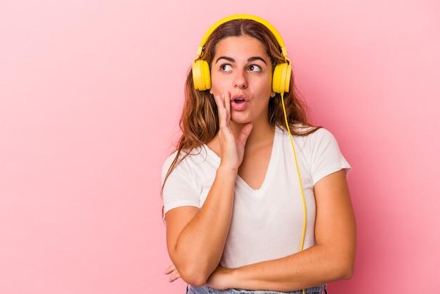 ピンクの背景で隔離の音楽を聞いている若い白人女性は秘密の熱いブレーキングニュースを言って脇を見ています