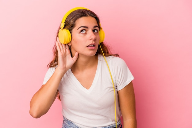 ゴシップを聴こうとしているピンクの背景に分離された音楽を聞いている若い白人女性。