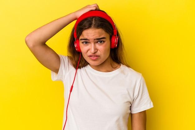 Молодая кавказская женщина, слушающая музыку на желтом фоне в шоке, вспомнила важную встречу.