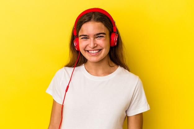 幸せ、笑顔、陽気な黄色の背景で隔離の音楽を聴いている若い白人女性。