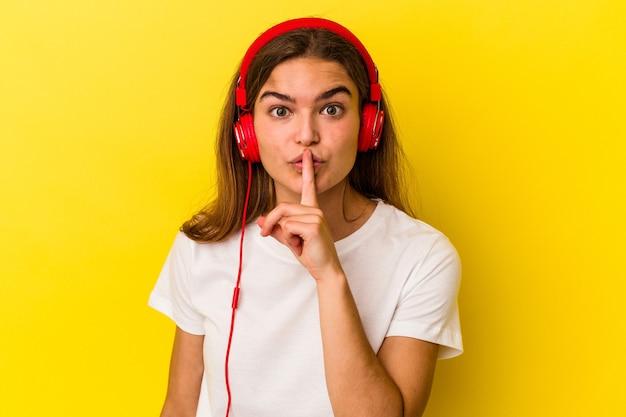 비밀을 유지하거나 침묵을 요구하는 노란색 배경에 고립 된 음악을 듣고 젊은 백인 여자.