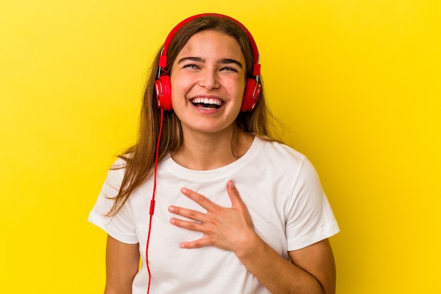 Молодая кавказская женщина, слушающая музыку на желтом фоне, громко смеется, держа руку на груди.