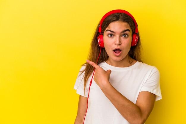 Молодая кавказская женщина слушает музыку на желтом фоне, указывая в сторону